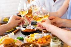 Руки при красное вино провозглашать над, который служат таблицей с едой стоковая фотография rf