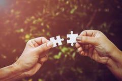 2 руки пробуя соединить пар озадачивают часть с пирофакелом предпосылки и света леса стоковое фото