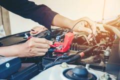Руки проверяют механика автомобиля батареи работая в обслуживании ремонта автомобилей Стоковые Изображения RF