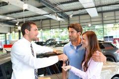 Руки продавца автомобилей над ключом автомобиля в автосалоне к cus Стоковое фото RF