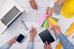 Руки профессиональных архитекторов обсуждая и работая с голубым Стоковое Изображение