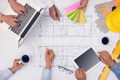 Руки профессиональных архитекторов обсуждая и работая с голубым Стоковое фото RF
