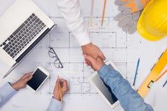 Руки профессиональных архитекторов обсуждая и работая с голубым Стоковая Фотография RF