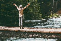 Руки путешественника женщины счастливые поднятые на мосте над приключением реки путешествуют Стоковые Фотографии RF