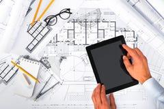 Руки плана строительства и мужских используя таблетку на светокопиях; Стоковое Изображение