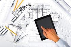 Руки плана строительства и мужских используя таблетку на светокопиях Стоковое Изображение