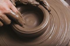 Руки работая на колесе гончарни стоковое фото