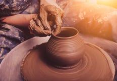 Руки работая на колесе гончарни стоковое фото rf