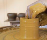 Руки работая с глиной на колесе гончара Стоковая Фотография