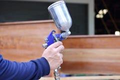 Руки работника держа краску для пульверизатора дают полный газ в домашней мастерской Стоковые Фотографии RF