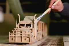 Руки работника крася выхлопные трубы деревянной тележки на запачканной предпосылке Стоковое Фото