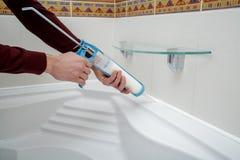 Руки работника прикладывая sealant силикона Стоковые Изображения