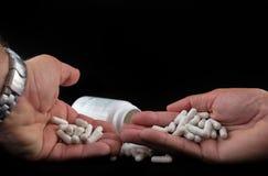 Руки 2 различных людей держа пилюльки с бутылкой таблетки на b Стоковое Изображение RF