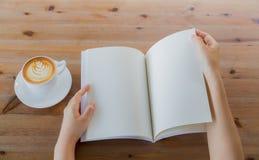 Руки раскрывают пустой каталог, кассеты, насмешку книги вверх на деревянной таблице Стоковое Изображение RF