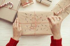 Руки раскрывая стильный подарок на рождество с красной лентой самомоднейше стоковая фотография rf