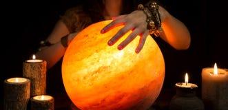 Руки рассказчика удачи, сияющего хрустального шара и свечей Стоковое Фото