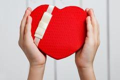 Руки ребенка давая красное сердце Стоковые Изображения RF