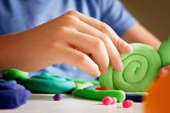 Руки ребенка делая игрушку вычисляют с глиной моделирования или пластилином Стоковые Изображения