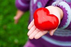 Руки ребенка держа томат Стоковая Фотография RF
