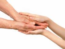 Руки детей обнимают старые руки Стоковая Фотография