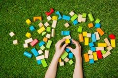Руки ребенка строя от блоков цвета деревянных Стоковое фото RF