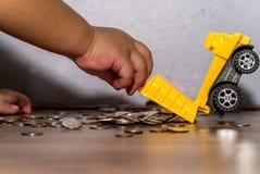 Руки ребенк держа тележку льют вне монетки тела Стоковое фото RF