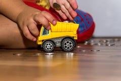 Руки ребенк загружая монетки к тележке Стоковая Фотография RF
