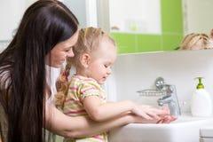 Руки ребенк моя с мылом в ванной комнате стоковое фото rf