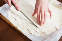 Руки режа магазин-купленное тесто Стоковые Фотографии RF