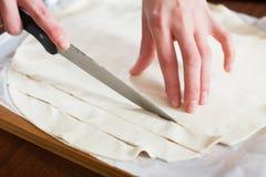 Руки режа магазин-купленное тесто Стоковое Фото