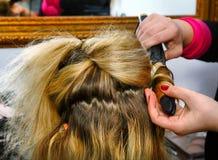 Руки дрессера волос делают скручиваемости с завивая схватами близко вверх по фото Стоковое Изображение RF