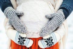 Руки родителей в связанных перчатках на животе беременной матери Стоковая Фотография RF