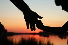 Руки родителя и ребенка силуэта Стоковые Изображения RF