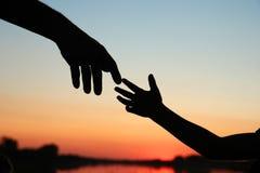 Руки родителя и ребенка силуэта Стоковая Фотография