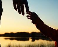 Руки родителя и ребенка силуэта Стоковые Изображения