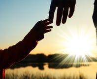 Руки родителя и ребенка силуэта Стоковое фото RF