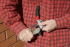 Руки садовника точат подрезая ножницы Чистка и Sha садовника стоковые изображения