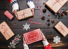 Руки семьи показывая подарок на рождество на деревянной предпосылке Стоковые Изображения RF