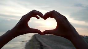 Руки сердца показывают на заходе солнца на пляже, взглядах солнца в камеру через форму знака влюбленности сделанного  акции видеоматериалы