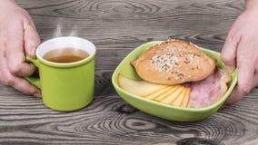 Руки служат плотный завтрак с горячим чаем стоковые фото