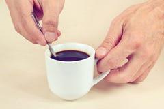 Руки смешивая при нежно тонизированная ложка горячего кофе в чашке, Стоковое Изображение