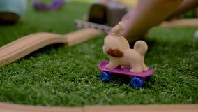 Руки собаки игрушки небольшой детской игры пластиковой на пурпурном скейтборде в комнате видеоматериал