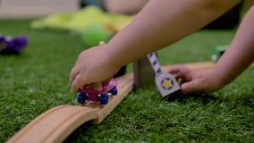 Руки собаки игрушки небольшой детской игры пластиковой на пурпурном скейтборде в комнате акции видеоматериалы