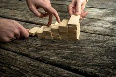 2 руки собирая лестницу деревянных колышков для трети дальше Стоковые Фото