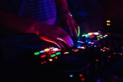 Руки современного смесителя DJ профессионального и доска музыки контролируя кнопок и уровней Стоковое Изображение