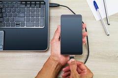 Руки соединяя smartphone к компьтер-книжке путем использование кабеля usb на деревянном столе с ручкой и бумагой Стоковая Фотография