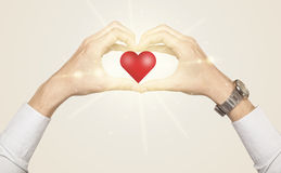 Руки создавая форму с сияющим сердцем Стоковое фото RF