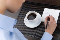 Руки сочинительства коммерсантки на бумажной салфетке на журнальном столе Стоковое Фото