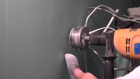 Руки со сверлом и кроной сверля круглое отверстие в штукатурной плите гипсокартона акции видеоматериалы