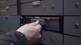 Руки старика кладут пластичный случай внутри клетки хранилища банка безопасной видеоматериал
